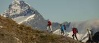 Trekkers on Buchanan peak with Mount Aspiring behind, walking above Matukituki valley, near Lake Wanaka | Colin Monteath