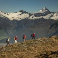 Trekkers on Buchanan peak with Mount Aspiring behind, walking above Matukituki valley, near Lake Wanaka   Colin Monteath
