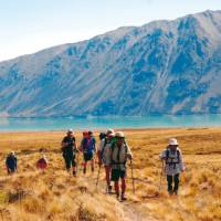 Trekking on the rolling tussock landscape of Mt Gerald station, with Lake Tekapo in the background | Chris Buykx